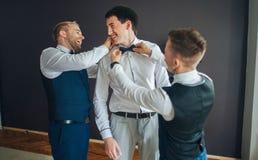 Groomsmen à moda que ajudam o noivo feliz que prepara-se no morni Imagem de Stock