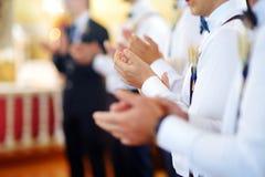 Groomsmen during catholic wedding ceremony Royalty Free Stock Image