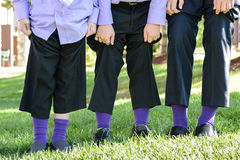 Groomsmen focus on Feet. Unique shot of groomsmen showing off the one time in their life that they are all wearing purple socks.  Quirky shot great for wedding Royalty Free Stock Photo