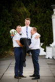Groomsmen hold the groom at the hands Stock Images