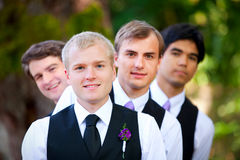 Groomsmen peeking from behind groom, outdoor Royalty Free Stock Images