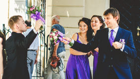 Groomsmen play like musketeers with bouquets Stock Photography