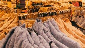 Groot aantal nieuwe warme modieuze sweaters die van verschillende kleuren op hangers in het winkelcentrum van de kledingsopslag h stock videobeelden