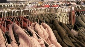 Groot aantal nieuwe warme modieuze sweaters die van verschillende kleuren op hangers in het winkelcentrum van de kledingsopslag h stock video