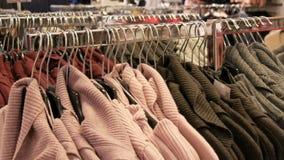 Groot aantal nieuwe warme modieuze sweaters die van verschillende kleuren op hangers in het winkelcentrum van de kledingsopslag h stock footage