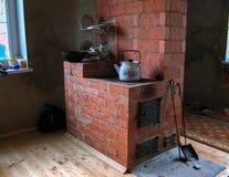 Groot baksteenfornuis in plattelandshuis in Rusland stock foto's