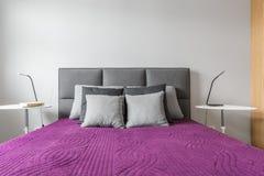 Groot bed met grijze hoofdkussens stock foto
