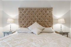 Groot bed op z'n gemak met nachtlampen in een slaapkamer Royalty-vrije Stock Foto's