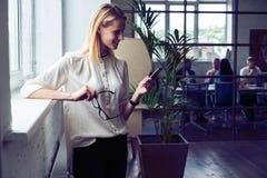 Groot bedrijfsbericht Zijaanzicht van vrolijke jonge mooie onderneemster in glazen die haar slimme telefoon met glimlach met behu stock foto's