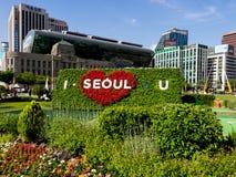 Groot bloembed met inschrijving tegen de achtergrond van een rood hart: 'U van I Seoel 'dichtbij Gwanghwamun-Vierkant in Seoel stock fotografie