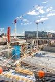 Groot bouwterrein op stedelijk gebied met kranen en stichtingen royalty-vrije stock afbeeldingen