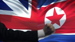 Groot-Brittannië versus de confrontatie van Noord-Korea, vuisten op vlagachtergrond, diplomatie stock video