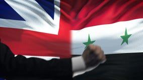Groot-Brittannië versus de confrontatie van Syrië, vuisten op vlagachtergrond, diplomatie stock video