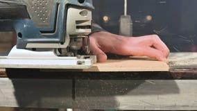 Groot close-up Een timmerman die een houten raad met een elektrische figuurzaag snijden o stock video