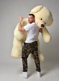 Groot de teddybeer zacht stuk speelgoed van de mensengreep als heden aan zijn meisje stock afbeeldingen