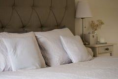 Groot en comfortabel bed met grote en kleine hoofdkussens met lijst naast en een lamp Royalty-vrije Stock Afbeeldingen