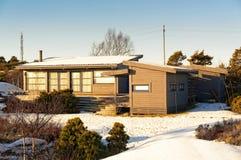 Groot grijs die plattelandshuisje op rotsen met sneeuw worden behandeld stock foto
