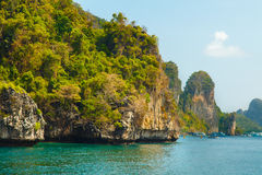 Groot groen rotseneiland op blauwe tropische overzees Royalty-vrije Stock Afbeelding