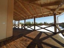 groot houten terras in traditioneel chalet met panoramisch rond vensters en pijnboombos stock fotografie