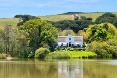 Groot huis naast meer en heuvels Royalty-vrije Stock Foto