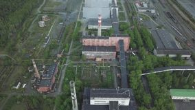 Groot industrieel landgoed met werkende schoorstenen en oude rode gebouwen dichtbij bossatellietbeeld stock video