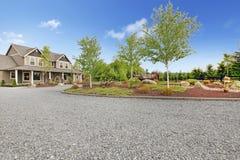 Groot landbouwbedrijfbuitenhuis met grintoprijlaan en groen landschap. Royalty-vrije Stock Foto