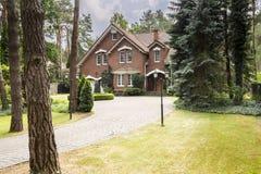 Groot, landelijk landgoed met baksteenvoorgevel en groen gazon die zich binnen bevinden stock fotografie