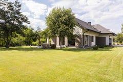 Groot losgemaakt huis met groene tuin stock afbeeldingen