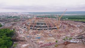 Groot modern stadion in aanbouw in achtergrondpanorama van moderne stad in de zomerdag stock video
