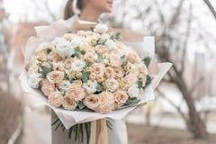 Groot Mooi boeket van gemengde bloemen in vrouwenhand Roze en witte kleur het werk van de bloemist bij een bloemwinkel stock foto's