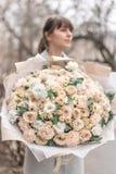 Groot Mooi boeket van gemengde bloemen in vrouwenhand Roze en witte kleur het werk van de bloemist bij een bloemwinkel royalty-vrije stock foto's