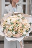 Groot Mooi boeket van gemengde bloemen in vrouwenhand Roze en witte kleur het werk van de bloemist bij een bloemwinkel stock afbeeldingen
