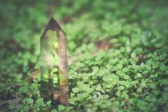 Groot mystiek gefacetteerd kwartskristal op een backgrou van de grasaard stock afbeelding