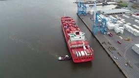 Groot rood geladen de containerschip die van de vrachtlading bij industriële stedelijke haven in het verbazende 4k luchtschot van stock footage