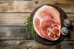 Groot ruw stuk van varkensvleesvlees met kruiden en kruid stock foto's