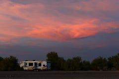 Groot rv alleen tegen zonsondergangwolken stock afbeeldingen
