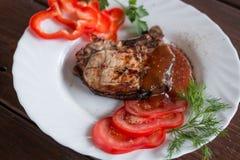 Groot sappig geroosterd lapje vlees met greens op de plaat stock foto