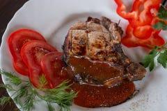 Groot sappig geroosterd lapje vlees met greens op de plaat stock afbeelding