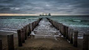 Groot schip die de houten pijler kruisen tijdens bewolkt weer bij het strand in Vlissingen, Zeeland, Holland, Nederland Royalty-vrije Stock Fotografie