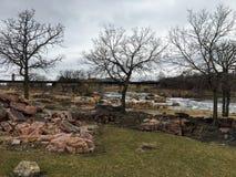 Groot Sioux River stroomt over rotsen in Sioux Falls South Dakota met meningen van het wild, ruïnes, parkwegen, de brug van het t Stock Foto