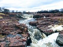 Groot Sioux River stroomt over rotsen in Sioux Falls South Dakota met meningen van het wild, ruïnes, parkwegen, de brug van het t Royalty-vrije Stock Foto