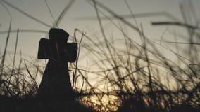Groot steenkruis in het gras bij zonsondergang stock videobeelden