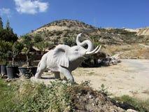 Groot steenstandbeeld van een olifant met een opgeheven boomstam Stock Foto