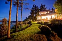 Groot twee verhaalhuis met veel lichten in de de zomeravond Royalty-vrije Stock Foto