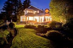 Groot twee verhaalhuis met veel lichten in de de zomeravond Stock Fotografie