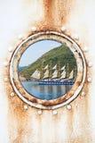 Groot varend schip achter ronde geroeste patrijspoort Stock Fotografie