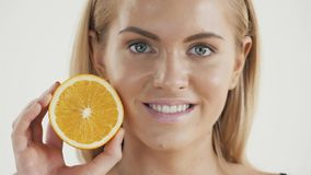 Groot voedsel voor een gezonde levensstijl Mooi jong shirtless de holdingsstuk van de blondevrouw van sinaasappel voor haar oog stock videobeelden