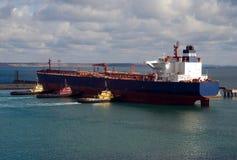 Groot vrachtschip en drie towboats in een haven Stock Foto's