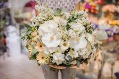 Groot wit boeket met reusachtige orchideeën in handen Stock Foto