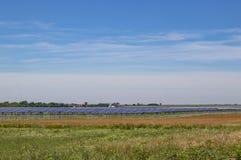 Groot zonnelandbouwbedrijf uit op de vlaktes met een lage horizon en landbouwbedrijf in afstand onder vrij blauwe hemel royalty-vrije stock afbeelding